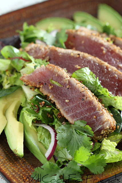Sesame crusted, pan seared Ahi tuna on a bed of fresh greens, lightly ...